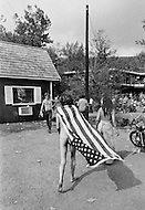 Middlefield, CT. August 1st and 2nd 1970.<br /> A nude man draped in the American Flag attends the 1970 Powder Ridge Festival in Middlefield.<br /> The Powder Ridge Rock Festival was scheduled to be held July 31, August 1 and August 2, 1970 at Powder Ridge Ski Area in Middlefield, Connecticut. A legal injunction forced the event to be canceled, keeping the musicians away; but a crowd of 30,000 attendees arrived anyway, to find no food, no entertainment, no adequate plumbing, and at least seventy drug dealers.