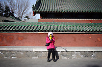 CHINA. A woman during Chinese New Year in Ditan Park in Beijing.  Chinese New Year, or Spring Festival, is the most important festival and holiday in the Chinese calendar In mainland China, many people use this holiday to visit family and friends and also visit local temples to offer prayers to their ancestors. The roots of Chinese New Year lie in combined influences from Buddhism, Taoism, Confucianism, and folk religions.  2008