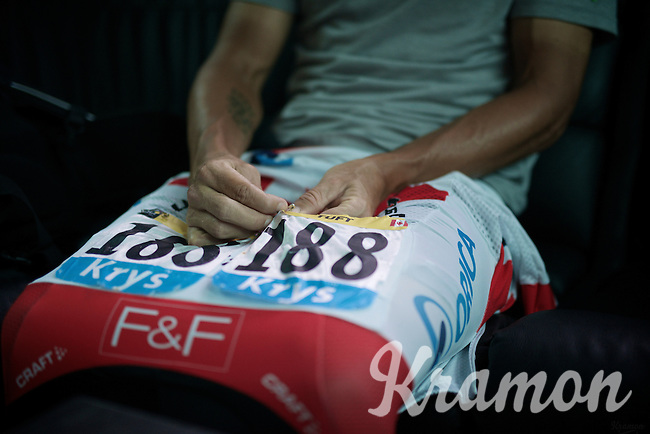 Svein Tuft (CAN/Orica-GreenEDGE) pinning down his race number in the teambus on the way to the start<br /> <br /> 2014 Tour de France<br /> stage 18: Pau - Hautacam (145km)