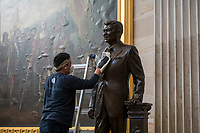 A man works on cleaning up a statue of former President Ronald Reagan in the Rotunda at the U.S. Capitol in Washington, DC, Tuesday, January 12, 2021. Credit: Rod Lamkey / CNP /MediaPunch