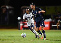 LAKE BUENA VISTA, FL - JULY 26: Roberto Puncec of Sporting KC is pressured by Yordy Reyna of Vancouver Whitecaps FC during a game between Vancouver Whitecaps and Sporting Kansas City at ESPN Wide World of Sports on July 26, 2020 in Lake Buena Vista, Florida.