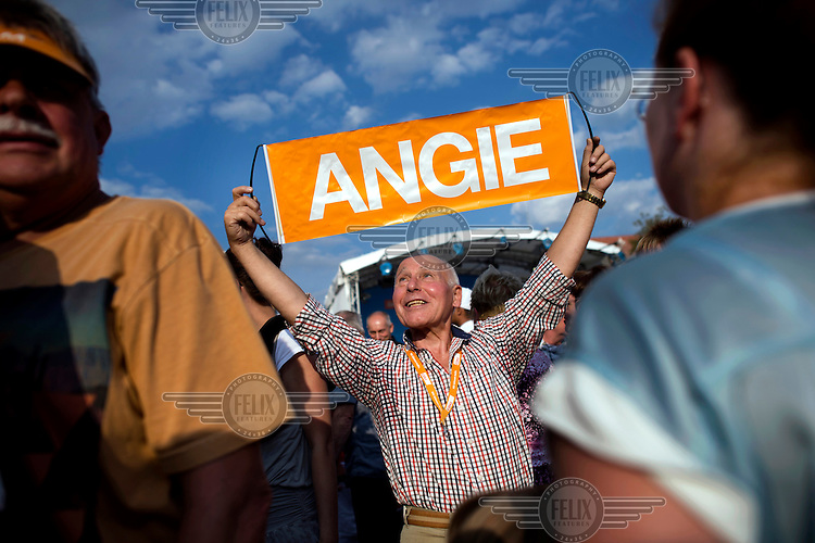 A man holds up an orange flag that reads: 'ANGIE', in reference to Angela Merkel leader of the CDU (The Christian Democratic Union of Germany), as she speaks to her supporters at a rally marking the start of campaigning for the 2013 election. Merkel, the current Chancellor of Germany, is seeking a third, four-year, term in office. A federal election is due to take place on 22 September 2013 to determine the make-up of the 18th Bundestag, Germany's legislative body.