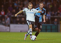 Kay Voser of Fulham under pressure from Michael Harriman of Wycombe Wanderers during the Capital One Cup match between Wycombe Wanderers and Fulham at Adams Park, High Wycombe, England on 11 August 2015. Photo by Andy Rowland.