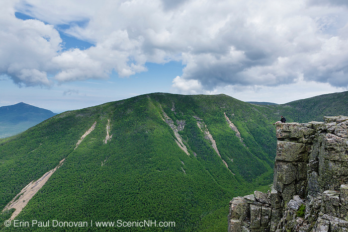 A hiker sitting on the summit of Bondcliff in the Pemigewasset Wilderness of New Hampshire during the summer months. West Bond is on the other side of Hellgate Ravine. Bondcliff, Mount Bond, and West Bond were named in 1876 for Professor G.P. Bond of Harvard University.