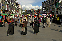 The famous Barkhor street where the old and new meets, traditional Tibeteans with their pryer wheel on the way to the Jokhang Temple ,Lhasa, Tibet,.The Jokhang Temple is one of Tibet's holiest shrines, originally .built in 647 A.D. in celebration of the marriage of the Tang Princess Wencheng and the Tubo King Songtsen Gampo. In front of the gate is a stone Tablet of Unity from the Tang Dynasty; inscribed are both Chinese characters and Tibetan script. Nearby is the stump of the willow tree said to have been planted by Princess Wencheng herself; two younger willow trees now flank the stump of the first tree...Located in the center of old Lhasa, the temple was built by craftsmen from Tibet, China, and Nepal and thus features different architectural styles. The temple is also the spiritual center of Tibet and the holiest destination for all Tibetan Buddhist pilgrims. In the central hall is the Jokhang's oldest and most precious object--a gold statue of a seated 12-year-old Sakyamuni. This is said to have been transported to Tibet by Princess Wencheng from her home in Changan in 700 A.D. Other precious antiques in the temple include a silk portrait of Buddha from the Tang Dynasty and a pearl gown and gold lamp from the Ming Dynasty. The three-leafed roof of the Jokhang offers splendid views of the bustling Barkhor market and across to the Potala Palace..
