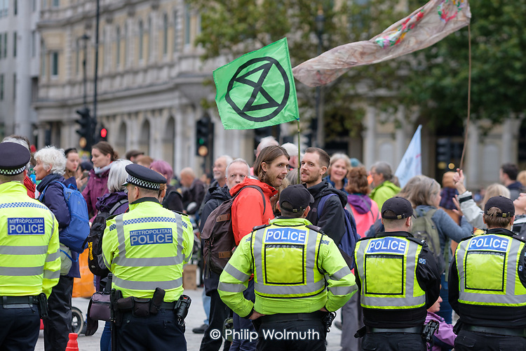 Police try to keep roads open for traffic as XR Extinction Rebellion London protesters occupy Trafalgar Square and attempt to block vehicle access.
