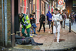 © Joel Goodman - 07973 332324 . 27/12/2015 . Wigan , UK . A paramedic tends to a man who has collapsed in the street . Revellers in Wigan enjoy Boxing Day drinks and clubbing in Wigan Wallgate . In recent years a tradition has been established in which put on fancy dress for a Boxing Day night out . Photo credit : Joel Goodman