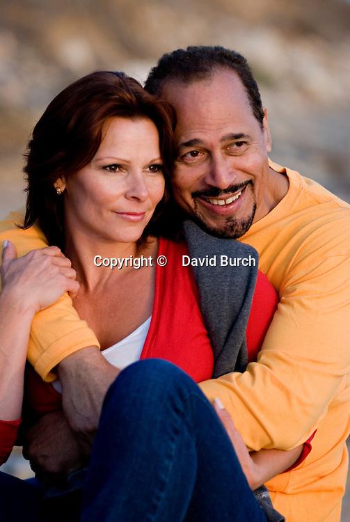 Mature couple smiling at beach, close-up