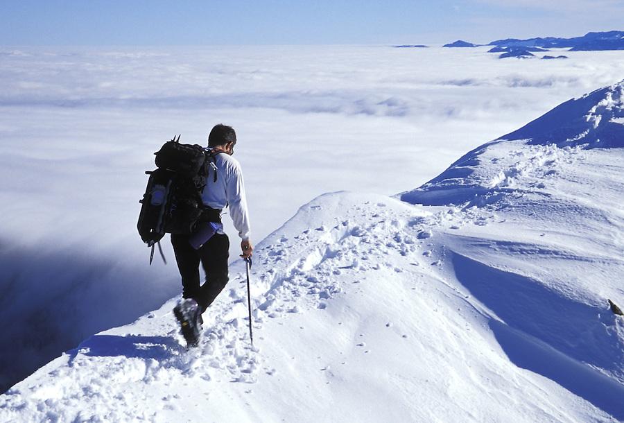 Man hiking along snowy ridge, Silver Peak, Mt Baker-Snoqualmie National Forest, Cascade Mountains, Washington