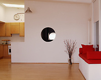 A partition wall with a circular window to one side of the open plan kitchen conceals the bedroom area