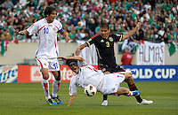 Costa Rica's Cristian Bolaños is knocked down by Mexico's Carlos Salcido.  Mexico defeated Costa Rica 4-1 at the 2011 CONCACAF Gold Cup at Soldier Field in Chicago, IL on June 12, 2011.