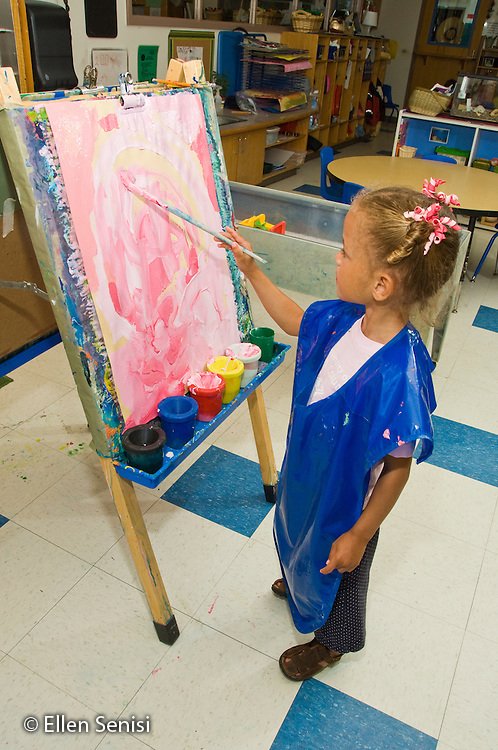 MR / College Park, Maryland.Center for Young Children, laboratory school within the College of Education at the University of Maryland. Full day developmental program of early childhood education for children of faculty, staff, and students at the university..Girl (4) paints at easel using only pink paint. .MR: All8.© Ellen B. Senisi