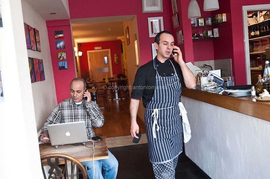 """Chenàbura 5 de martzu de su 2010 Londra (Regnu Unidu) <br /> Antonello Serra, nàschidu in Aristanis in su 1961, si nche tràmudat a Londra in su 1995 pro traballare comente coghineri e pro ga-antire curas addatas a sa fìgia Giòrgia. In su 2006, cun su connadu Roberto Brai, aberit, in su cuarteri de Brockley in Londra, su ristorante """"Le Querce"""". Inoghe est fotografadu, paris cun Roberto, in intro de su ristorante ammaniende su traballu de sa die. <br /> <br /> Venerdì 5 marzo 2010 Londra (Regno Unito) <br /> Antonello Serra, nato ad Oristano nel 1961, si trasferisce a Londra nel 1995 per lavorare come cuoco e per garantire cure adeguate a sua figlia Giorgia. Nel 2006, insieme al cognato Roberto Brai, apre, nel quartiere di Brockley a Londra, il ristorante """"Le Querce"""". Qui è ritratto, insieme a Roberto, all'interno del ristorante mentre organizzano il lavoro del giorno. <br /> Friday 5th March 2010 London (United Kingdom) <br /> Antonello Serra, born in Oristano in 1961, moves to London in 1995 to work as a chef and to ensure adequate healthcare for his daughter Giorgia. In 2006, together with his brother in law Roberto Brai, he opens, in the neighbourhood of Brockley in London, the restaurant """"Le Querce"""". Here he is portrayed together with Roberto, inside the restaurant while they organise the work for the day."""
