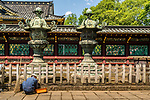 A worker at the entrance of Toshogu Shinto shrine located in Ueno, Tokyo, Japan. First established in 1627 by Tōdō Takatora and renovated in 1651 by Tokugawa Iemitsu, the shrine remains mostly intact since that time, making it a great example of Shinto architecture of the Edo period.