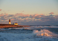 The setting sun casts a pink glow on crashing waves at Point Judith Lighthouse