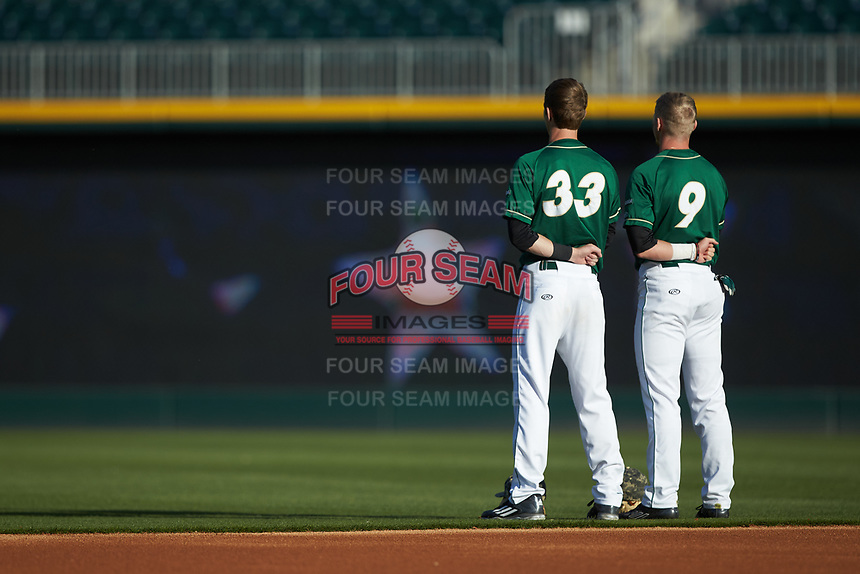 Hunter Jones (33) and Brett Netzer (9) of the Charlotte 49ers stand for the National Anthem prior to the game against the North Carolina State Wolfpack at BB&T Ballpark on March 29, 2016 in Charlotte, North Carolina. The Wolfpack defeated the 49ers 7-1.  (Brian Westerholt/Four Seam Images)
