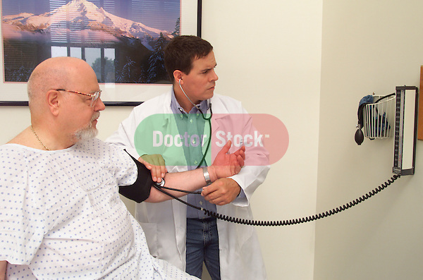 young male doctor conducting a routine blood pressure examination of an older, elder male patient