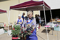 """Volunteer Diane Callahan carries items out to a customer's car, Thursday, October 7, 2021 during a rummage sale at the Central United Methodist Church in Rogers. The annual event returns with a larger selection for shoppers following a break due to the covid-19 pandemic. """"We're inundated this year,"""" said Carol Hartman, president of the  Central United Methodist Women. """"[donors] stayed home and cleaned out their houses, and so they had lots to donate this year."""" Items included houseware and clothing as well as unique items like an armoire of clothing from the 1880's and a Gucci watch. All funds from the sale will go to support projects for women and children in the community and world wide. Check out nwaonline.com/211008Daily/ for today's photo gallery. <br /> (NWA Democrat-Gazette/Charlie Kaijo)"""