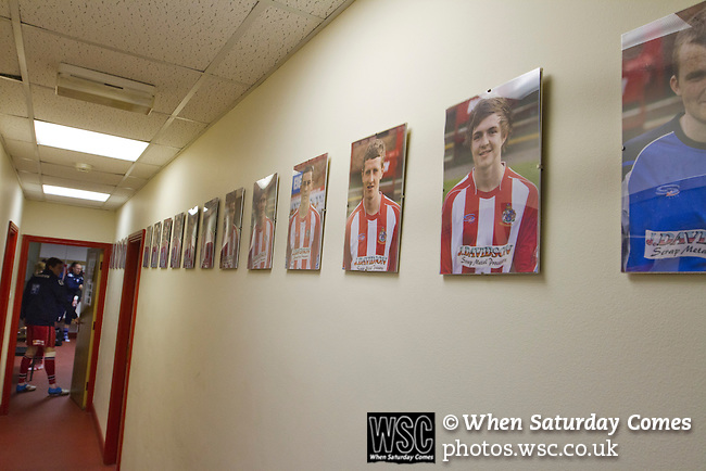 Altrincham 2 Worcester City 0, 23/03/2013. Moss Lane, Blue Square Bet North. A row of photographs of current home team players in a corridor inside the stadium before the Blue Square Bet North fixture between Altrincham and Worcester City at Moss Lane, Altrincham. The home team won the match 2-0 watched by 777 spectators on a day when most non-League football in England was cancelled due to adverse weather. Altrincham were historically one of the major English non-League teams but have never been promoted to the Football League. Photo by Colin McPherson.