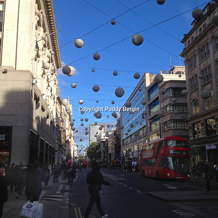 Lights in Oxford street, London. Oxford Street is a major road in the City of Westminster in the West End of London, running from Marble Arch to Tottenham Court Road via Oxford Circus. It is Europe's busiest shopping street, with around half a million daily visitors, and as of 2012 had approximately 300 shops. It is designated as part of the A40, a major road between London and Fishguard, though it is not signed as such, and traffic is regularly restricted to buses and taxis.<br /> <br /> The road was originally a Roman road, part of the Via Trinobantina between Essex and Hampshire via London. It was known as Tyburn Road through the Middle Ages and was once notorious as a street where prisoners from Newgate Prison would be transported towards a public hanging. It became known as Oxford Road and then Oxford Street in the 18th century, and began to change character from a residential street to commercial and retail purposes by the late 19th century, also attracting street traders, confidence tricksters and prostitution. The first department stores in Britain opened on Oxford Street in the early 20th century, including Selfridges, John Lewis and HMV. Unlike nearby shopping streets such as Bond Street, it has retained an element of downmarket street trading alongside more prestigious retail stores. The street suffered heavy bombing during World War II, and several longstanding stores including John Lewis were completely destroyed and rebuilt from scratch.<br /> <br /> Stock Photo by Paddy Bergin