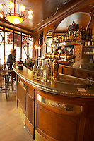 The curved bar zinc brass beer and water taps and water carafes blurred people sitting on high chairs drinking Bottles and glasses on shelves behind the bar. The Bistrot du Peintre is an old fashioned Paris café cafe bar restaurant of art nouveau design with polished brass, mirrors and old signs