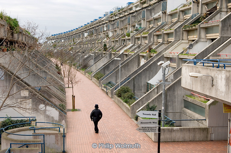 A police officer on patrol in Rowley Way, on Camden Council's  Alexandra and Ainsworth Estate, London.