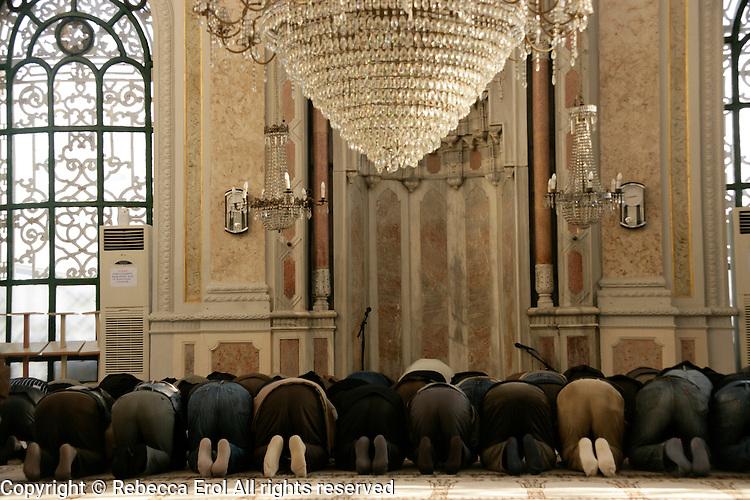 Muslim men praying at the Buyuk Mecidiye mosque in Ortakoy, Istanbul, Turkey