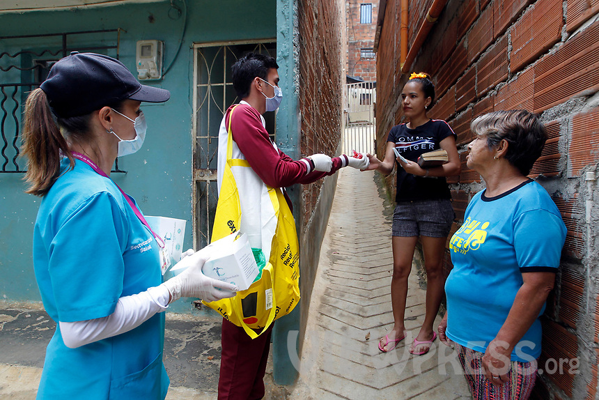 MEDELLIN, COLOMBIA-MAY 29: A health worker distributes facial masks in the houses and premises, in the neighborhood of Santa Cruz in Medellín, Colombia, on May 29, 2020. The mayor of Medellín and the private company offer a mask facial, antibacterial gel and alcohol for city communes As a preventive measure against the new coronavirus COVID-19. (Photo by Fredy Builes / VIEWpress via Getty Images)