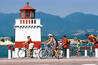 Stanley Park, Vancouver, BC, British Columbia, Canada - Cyclists cycling on Seawall past Brockton Point Lighthouse, in Summer - North Vancouver and North Shore Mountains in background