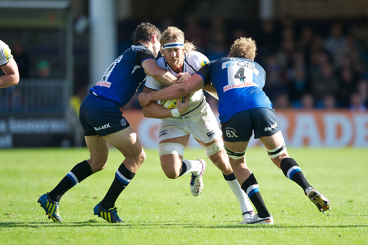 Andy Powell of Sale Sharks is tackled by (L-R) Stephen Donald and Stuart Hooper of Bath Rugby during the Aviva Premiership match between Bath Rugby and Sale Sharks at the Recreation Ground on Saturday 29th September 2012 (Photo by Rob Munro)