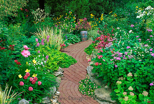 Scalloping brick pathway through blooming garden and painted Mexican vase, Missouri USA