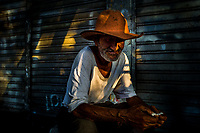 A Colombian vendor, wearing a cowboy hat, hides in the shadow in Plaza Minorista market in Medellín, Colombia, 16 December 2018.