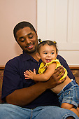 MR / Schenectady, NY. Father (22, African American) holds infant daughter (girl, 10 months, African American & Caucasian) as she smiles and claps her hands. MR: Dal7, Dal4. ID: AL-HD. © Ellen B. Senisi