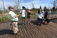 """DAY AT OSAGE<br />Steve Kick, a Northwest Arkansas Master Naturalist, leads Saturday Oct 9 2021 a tour of the wetland area at Osage Park in Bentonville. The tours were part of """"A Day at Osage Park"""" celebration held at the Bentonville park at 700 S.W. 16th St near Lake Bentonville. The event showcased a variety of activities available at the park including pickleball, archery, food, and strolling on a boardwalk above the wetland. Conservation groups and vendors had exhibits. Kick explains the role of the weland to Kyle Sullivan (from left), Lindsey Sullivan, Miranda Mangano and Glenn Mangano. Go to nwaonline.com/211010Daily/ to see more photos. <br />(NWA Democrat-Gazette)"""