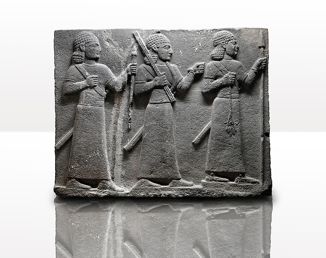 Picture & image of a Neo-Hittite orthostat of 3 warriors from the legend of Gilgamesh from Karkamis,, Turkey. Museum of Anatolian Civilisations, Ankara. The warrior on the far left holds a spear in one hand and the branch of a tree in the other. The middle warrior has a clenched fist an carries an impliment over his shoulder. The warrior on the far right carries a saff. All 3 are wearing swords.  4
