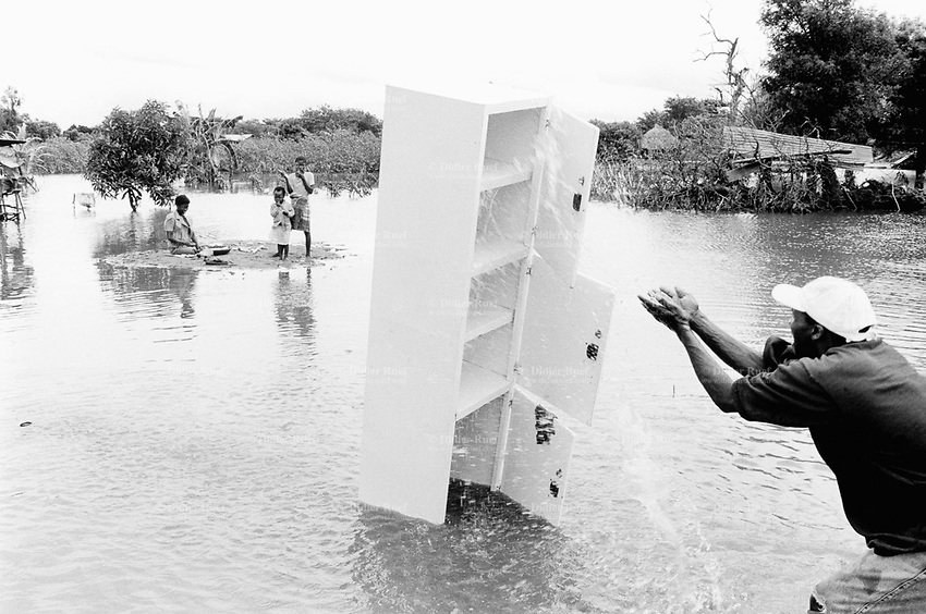"""Mozambique. Province of Gaza. Chokwe. The Limpopo river has flooded the whole town.""""Tercero Barrio"""", one of its districts, was heavily flooded and its population suffered the largest destruction and losses. A man washes the mud away from his cupboard. © 2000 Didier Ruef"""
