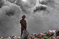 A Nicaraguan boy works on the burning pile of garbage in the garbage dump La Chureca, Managua, Nicaragua, 4 November 2004. La Chureca is the biggest garbage dump in Central America. Hundreds of trash recollectors search in tons of smouldering garbage mainly metals (copper, aluminium), others concentrate on glass which is cheap, but in bigger amount. The majority of the recyclers are families with children for whom recycling is a regular job. The children very often eat the food they find on the dump, none of them goes to school, they suffer from skin diseases, they have high levels of lead and DDT in blood.