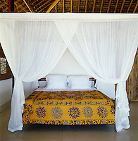 The four-poster bed has Balinese mosquito nets and the bed cover is an antique suzani