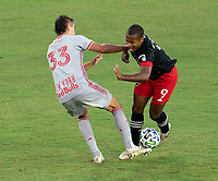 WASHINGTON, DC - SEPTEMBER 12: Aaron Long #33 of the New York Red Bulls and Ola Kamara #9 of D.C. United fight for the ball during a game between New York Red Bulls and D.C. United at Audi Field on September 12, 2020 in Washington, DC.