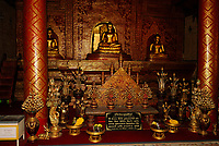 Altar covered with small Buddha statues covered with gold at Wat Phra Singh Buddhist temple in Chiang Mai city, Thailand, Southeast Asia. Construction on Wat Phra Singh began in 1345 when King Phayu, the fifth king of the Mangrai dynasty, had a chedi built to house the ashes of his father King Kham Fu.