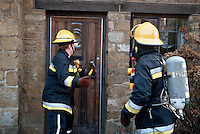 Firefighters, in breathing apparatus, are preparing to enter a thatched house on fire. They are attempting to knock the front door down using a sledgehammer. This image may only be used to portray the subject in a positive manner..©shoutpictures.com..john@shoutpictures.com