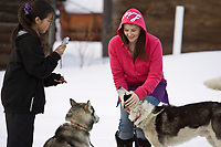 Takotna residents Janann Capsul takes a photo while Misty Wachter pets a dog from Susan Ramstead's team on Thursday evening during Iditarod 2008