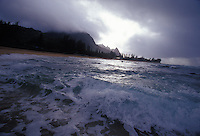 Waves breaking in whitewater on a cloudy day at Haena Beach, North Shore of Kauai, with Bali Hai Peaks in background.