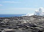 Frozen lava fields and smoke plume from lava entering the ocean in Hawaii Volcanoes National Park.