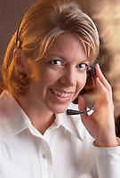 A smiling woman talking into a telephone headset.