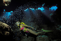 scuba diver explores Minnow Cave, a cavern full of glass minnows or silversides Berry Islands, Bahamas, Caribbean (Western Atlantic Ocean)
