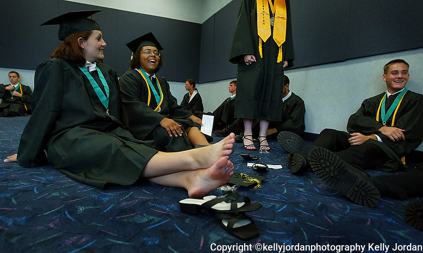 Pine Ridge High School graduates Ashley Sweet, left, and Cristina Pitter sit on the floor and rest their feet as they wait for graduation ceremonies to begin for the Class of 2004 Sunday afternoon, May 23, 2004 at the Ocean Center in Daytona Beach.(kelly Jordan)