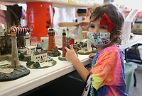 """Harper Tucker, 4, of Rogers picks out a lighthouse figurine, Thursday, October 7, 2021 during a rummage sale at the Central United Methodist Church in Rogers. The annual event returns with a larger selection for shoppers following a break due to the covid-19 pandemic. """"We're inundated this year,"""" said Carol Hartman, president of the  Central United Methodist Women. """"[donors] stayed home and cleaned out their houses, and so they had lots to donate this year."""" Items included houseware and clothing as well as unique items like an armoire of clothing from the 1880's and a Gucci watch. All funds from the sale will go to support projects for women and children in the community and world wide. Check out nwaonline.com/211008Daily/ for today's photo gallery. <br /> (NWA Democrat-Gazette/Charlie Kaijo)"""