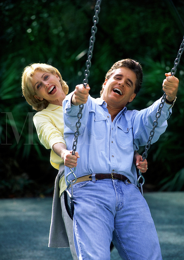 A smiling couple play on a swing.