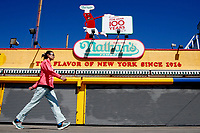 BROOKLYN - NEW YORK - APRIL 08: A woman walks in front of Nathan's Famous at Coney Island on April 08, 2021 in New York. After 18 months of closure due to the Coronavirus pandemic, Coney Island parks will welcome visitors taking safety restrictions including physical distancing through reduced capacity. (Photo by John Smith/VIEWpress)